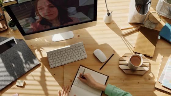 Siedząca przy biurku osoba robiąca notatki oglądająca webinar na monitorze