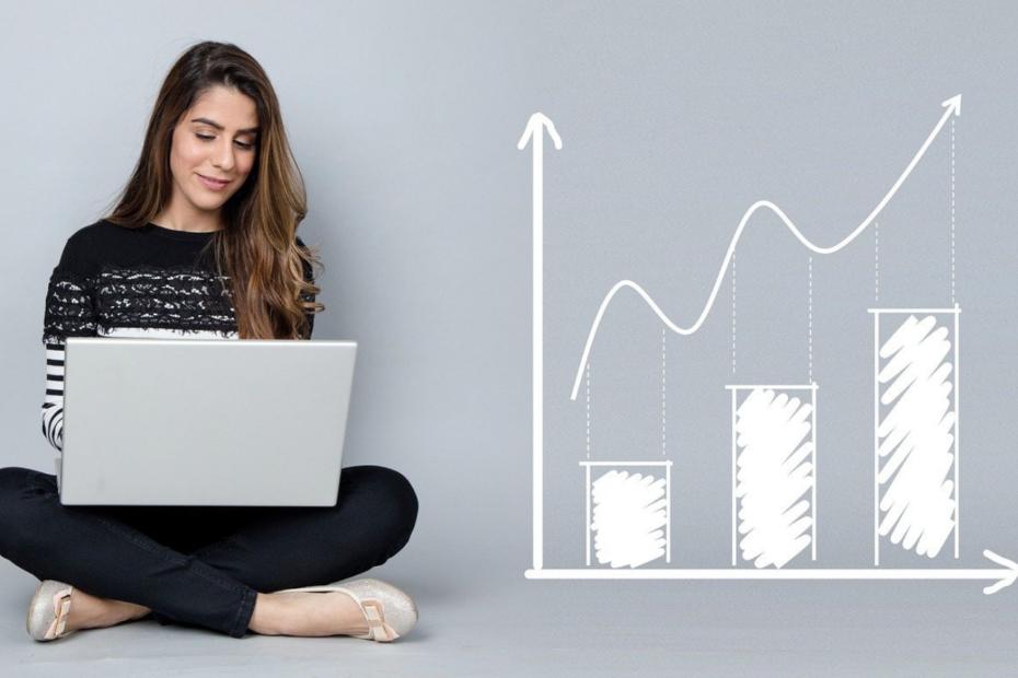 Siedzą kobieta pracująca na laptopie obok niej wykres symbolizujący wzrost