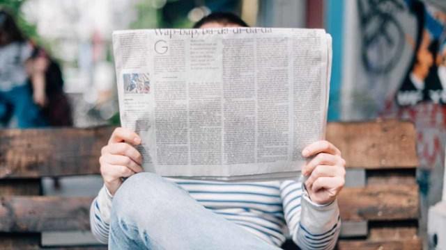 siedzący mężczyzna czytający rozłożoną gazetę