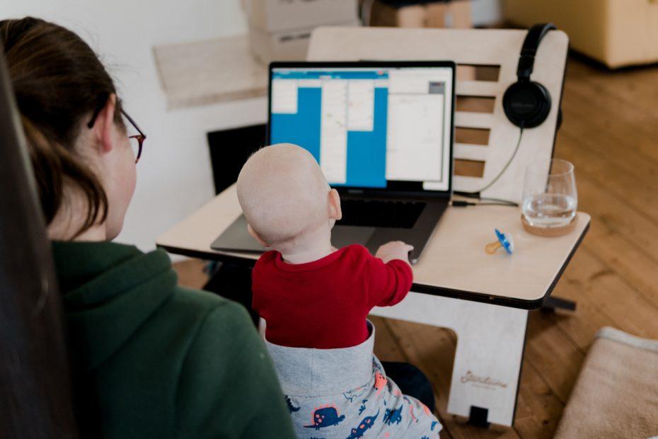 Mama trzymająca dziecko na kolanach pracująca zdlanie przy komputerze jako Wirtualna Asystentka