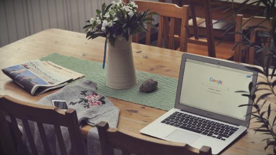 Jadalniany drewniany stół na którym stoi laptop z wyśwetloną główną stroną google, obok gazeta i kwiaty
